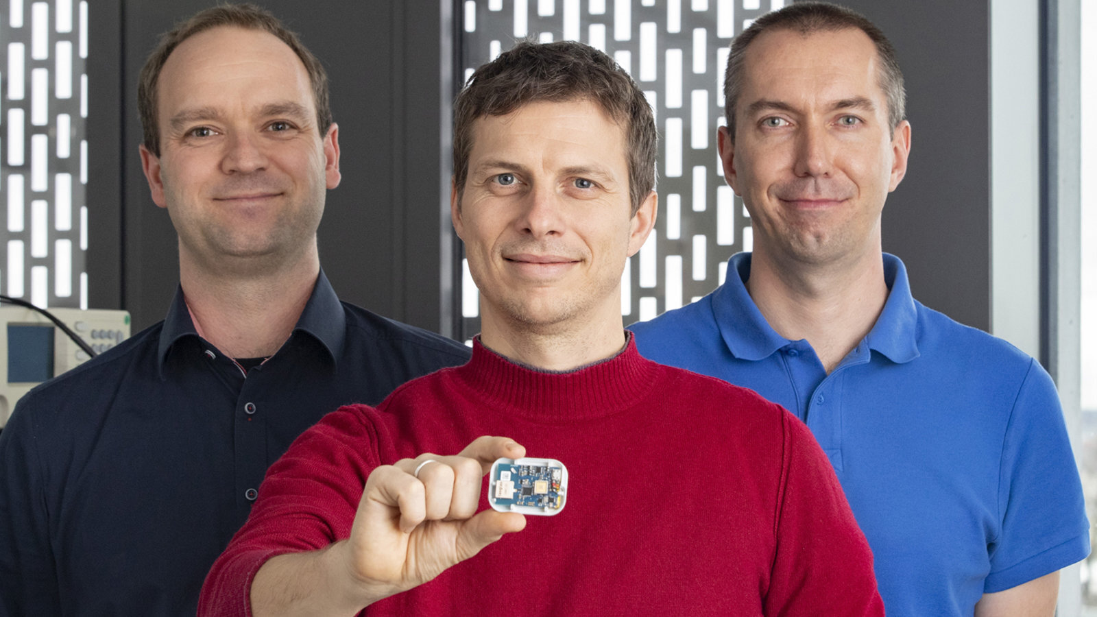 Three men. The man in the middle is holding a localizing chip.