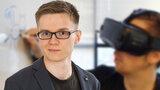 EIn junger Mann im Sakko. Dahinter ein junger Mann mit VR-.Brille.