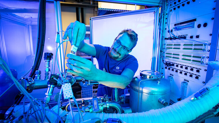 A man in a t-shirt and glasses works in a laboratory.