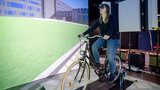A young woman sits on a bicycle inside of an VR Cave.