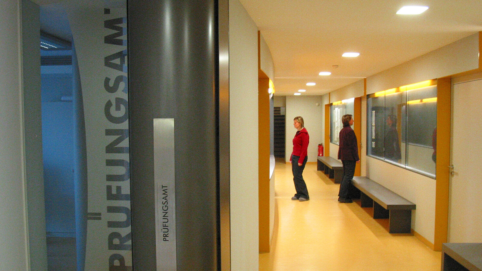 "Image of a sign reading ""Prüfungsamt"" next to two people waiting in a hallway."