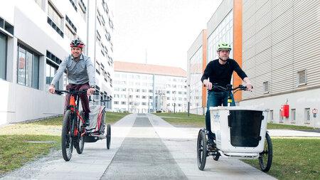 Zwei Mäner fahren nebeneinander auf Lastenfahrrädern.