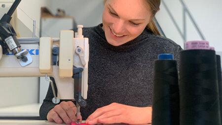 Junge Frau arbeitet an einer Nähmaschine