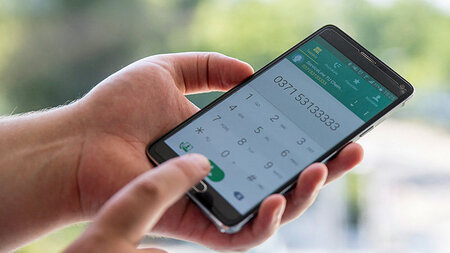 Person hält Smartphone in der Hand, im Display steht eine Telefonnummer
