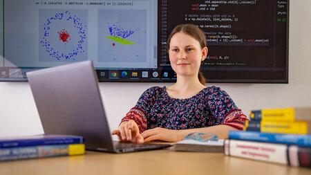 Junge Frau arbeitet an einem Laptop, im Hintergrund ist der Ausschnitt einer Darstellung auf einem großen Bildschirm zu sehen.