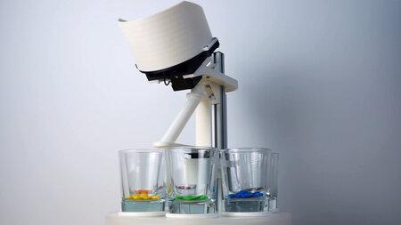 Ein kleiner Automat mit Gläsern auf einem Drehteller, in denen bunte Schokolinsen liegen.