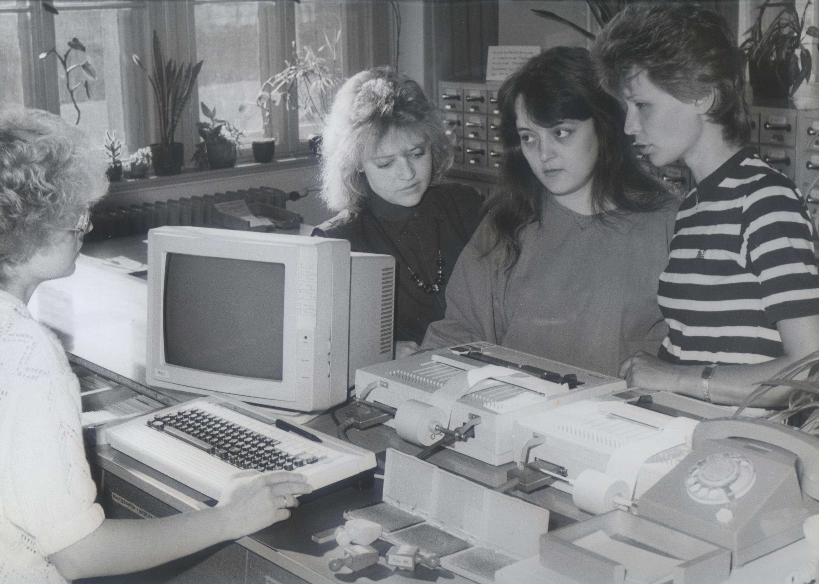 Foto: Bibliothekrin sitzt am ersten PC + Drucker und gegenüber stehen 3 junge Frauen, 1988 © Barbara Kretschmar